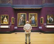 Man standing looking at portraits Fitzwilliam Museum © VisitBritain / Jon Attenborough